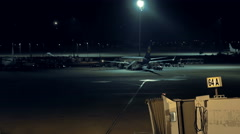 Airplane is standing still at the airport at night Stock Footage