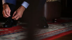 Bridegroom ties laces on his black patent shoes - stock footage