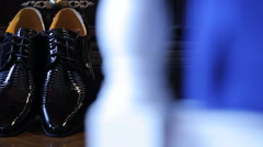 Shining black bridal shoes stand on floor near wooden wardrobe Stock Footage