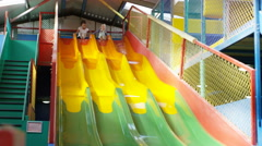 4K Little girls having fun on the slide at indoor playground Stock Footage