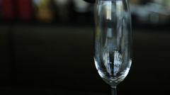 Sparkling champagne is filling crystal wine glass that stands on table Stock Footage