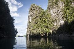 Rugged limestone islands frame an Indonesian pinisi schooner. Stock Photos