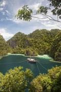 Rugged limestone islands frame an Indonesian pinisi schooner. - stock photo