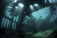 Bright sunlight pierces a shallow World War II shipwreck. Stock Photos
