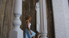 Beautiful blonde woman climbs on small stepladder to take her wedding dress Stock Footage