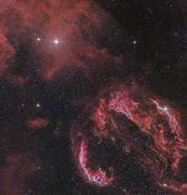 The Veil Nebula in the constellation Cygnus glows red. - stock photo
