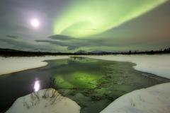 Aurora borealis over a creek by Fish Lake, Whitehorse, Yukon, Canada. Kuvituskuvat