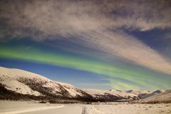 Aurora borealis with moonlight over Ogilvie Mountains, Canada. Stock Photos
