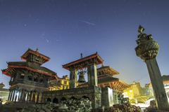 A meteor streaks the sky above Bhaktapur Durbar Square of Nepal. Stock Photos