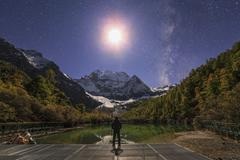 The Milky Way and waxing cresent moon over Mount Chenrezig in China. Stock Photos