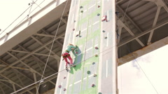 Little girl climbing rock wall while climbing competition Stock Footage