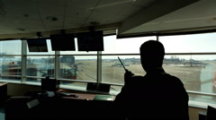 In airport air traffic controller is looking into distance holding radio Stock Footage