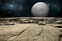 A cratered moon rises over a rocky and barren alien world. - stock illustration