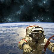 A cosmonaut floats in space above Earth. Stock Photos
