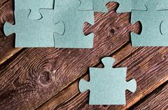 Incomplete puzzles lying on wooden rustic boards. Stock Photos