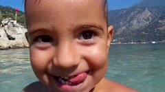 Kid in the sea comes up and peeps into camera - stock footage
