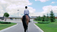 A guy rides on a horse to the arena Stock Footage
