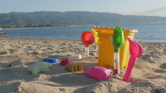 Colorful plastic toys for game - bucket and shovels on sandy beach close up. Stock Footage