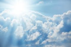 Bright sun shines among the white clouds Stock Photos