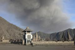 Ash cloud passing over temple at foot of Mount Bromo Volcano, Tengger Caldera, Stock Photos