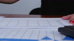 Woman accepts the calculations and puts the stamp of refusal. Close up Stock Footage
