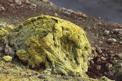 Lava bomb coated in yellow sulphurous fumarole deposits. Stock Photos
