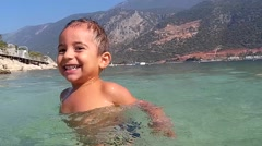 Kid gambles in the sea shot above and under water Stock Footage