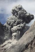 Ash cloud rises from crater of Batu Tara volcano, Indonesia. Stock Photos
