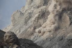 Rockfall on flank of Rerombola lava dome of Paluweh volcano, Indonesia. - stock photo