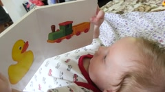 Baby Playing With Story Book Stock Footage
