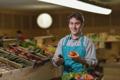 Grocery clerk juggling with tomatoes in supermarket store Stock Photos
