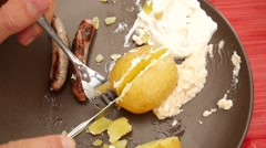 Grilled sausages and potatoes are cut by knife and fork on plate Stock Footage