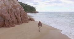Aerial of a man walking on a tropical beach, New Zealand Stock Footage