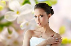 beautiful woman with earring, ring and pendant - stock photo