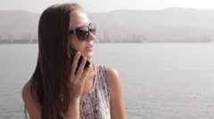Young woman talk on mobile phone at seafront Stock Footage