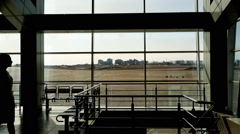 In airport waiting area beautiful female is walking slowly up and down Stock Footage