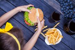 Child girl eating a burger fast food at the table. the view from the top Stock Photos