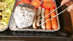 Grilling bratwurst and red sausages, tomatoes, lump in alu foil and peppers Stock Footage