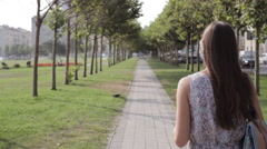 Young woman with a book walking in park. Stock Footage
