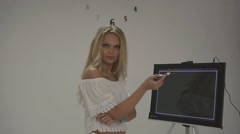 Attractive blonde girl in white top tries to find logo for dental health company - stock footage