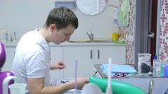 Young male dentist prepared to work at your workplace, choosing right tools Stock Footage