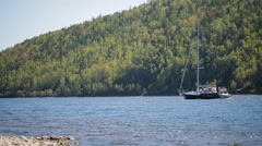 Boat empty-mast sailing against current of a river on background of slope mixed Stock Footage