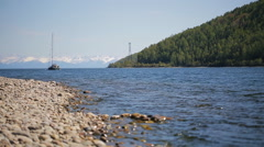 A sailing boat moves away from pebbly shore in background of a chain of Stock Footage
