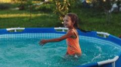Little Girl Splash in the Pool in the Garden Stock Footage