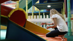 4K Mother waits for her daughter at bottom of slide in indoor playground Stock Footage