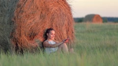 Beautiful young girl resting at stacks of hay at sunset Stock Footage