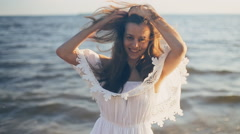 Girl smiling on the beach and straightens hair Stock Footage