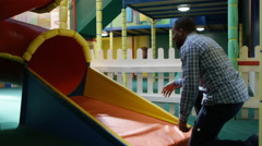 4K Father waits for his daughter at bottom of slide in indoor playground Stock Footage