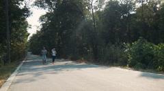 Couple jogging along asphalt road in forest Stock Footage
