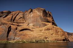 Steep cliffs guard the Colorado River near Lees Ferry, Arizona. - stock photo